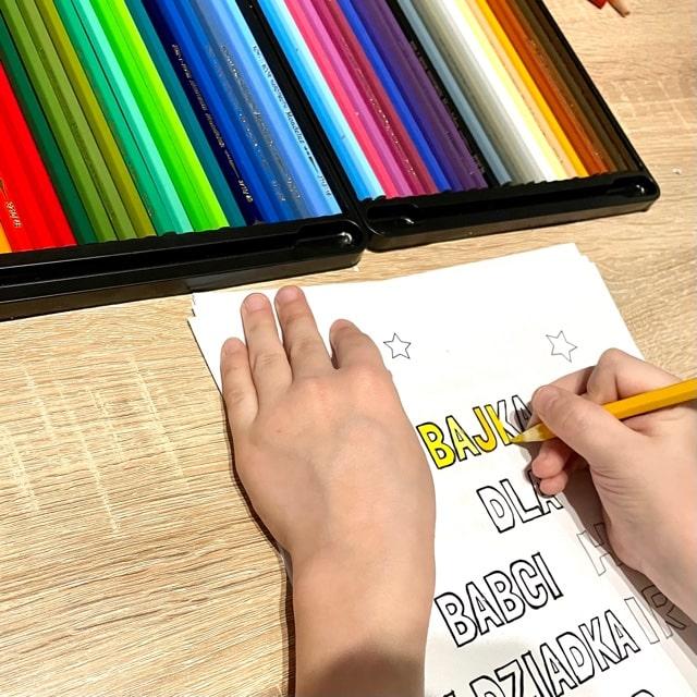 Dziecko pisze koloruje bajkę dla babci i dziadka