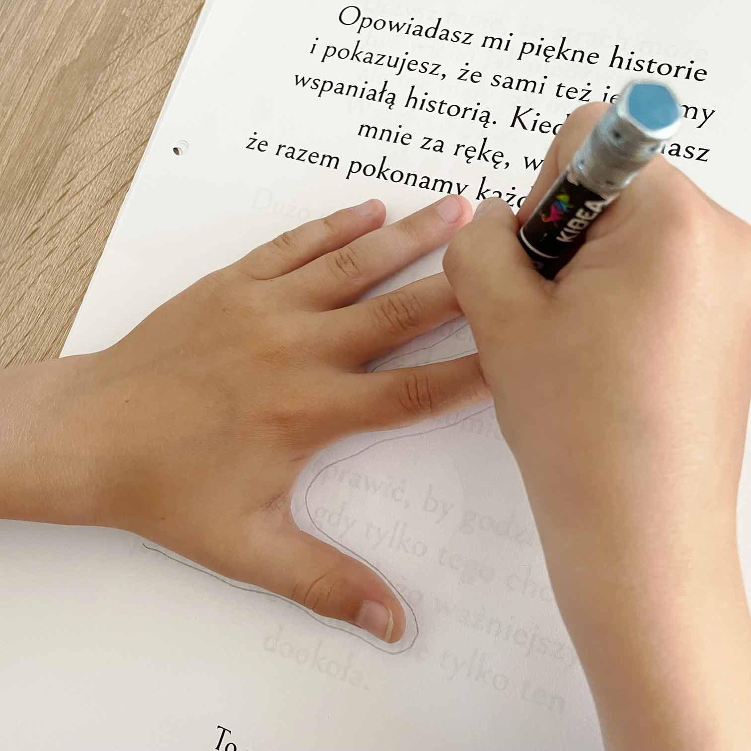 Dziecko robi prezent dla taty - rysuje swoją dłoń