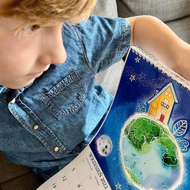 chłopiec przegląda swój kosmiczny kalendarz dla dzieci