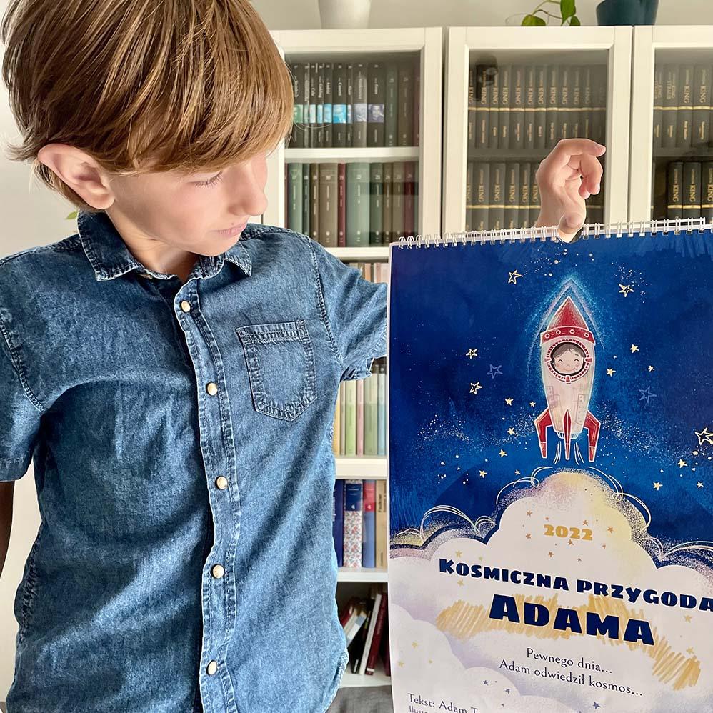 chłopiec trzyma swój kosmiczny ścienny kalendarz dla dzieci